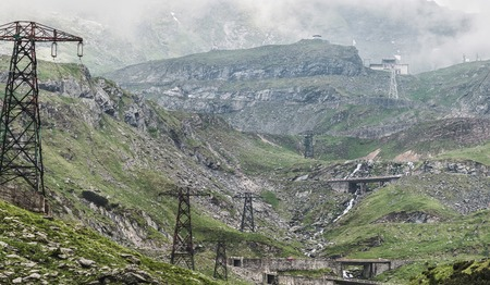 View of the Fagaras mountains with famous and dangerous Transfagarasan road on the height in Carpathians, Romania, spectacular wilderness scenery.