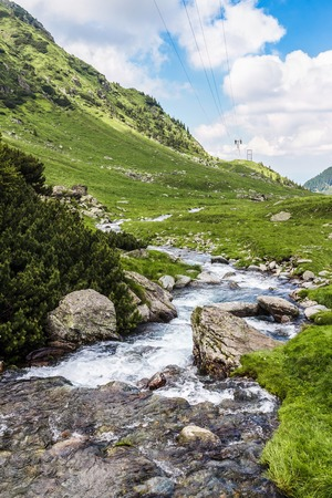 View of the Fagaras mountains and water stream in Carpathians, Romania, spectacular wilderness scenery.