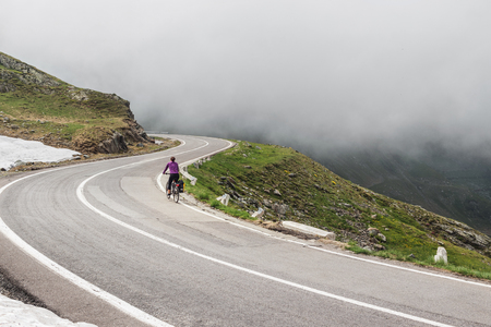 Woman on a bike travel on the most famous and dangerous road in Europe is a Transfagarasan road in Carpathian mountains, Romania. Stock Photo