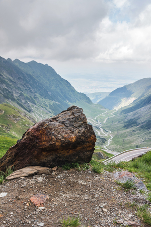 Big stone on foreground and view of the famous Transfagarasan road in Carpathian mountains, Romania.