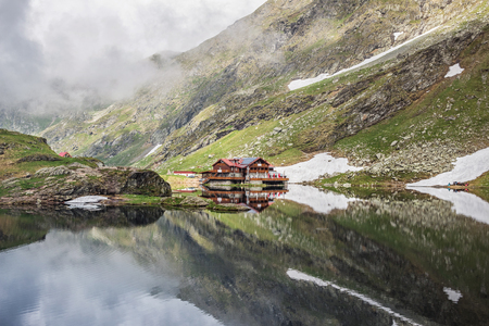 Nature landscape of amazing glacier lake Balea with house on shore and Fagaras mountains with white strips of snow reflected in the water at Carpathians, Romania.
