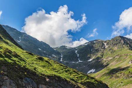 Mountain landscape of the high rocky Fagaras mountains with famous Transfagarasan road in Carpathians, Romania.