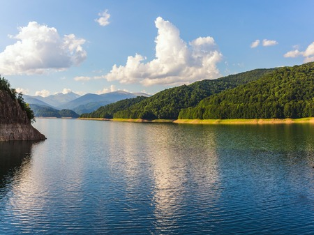 Amazing mountain lake Vidraru in Carpathian mountains at Romania, wild nature landscape in the summer.