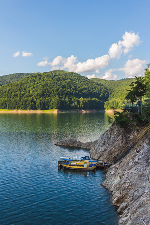 Amazing mountain lake Vidraru in Carpathian mountains at Romania, wild nature landscape in the summer.