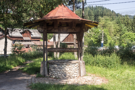 Ancient stone draw-well at Carpathian village in Romania.