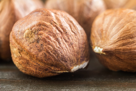 Raw brown hazelnut on wooden planks, macro image. Stock Photo