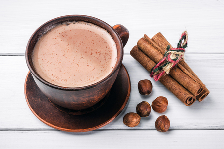Hot cocoa with milk in brown clay cup, hazelnut and cinnamon sticks on table of white wooden planks.