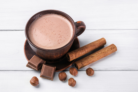 Hot cocoa with milk in brown clay cup, broken chocolate cubes, hazelnut and cinnamon sticks on white wooden planks.