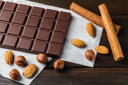 Bitter, dark chocolate bar, almond, hazelnut and cinnamon stick on wooden background.