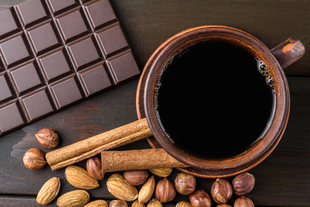 Hot black coffee in brown clay cup, dark chocolate bar, almond, hazelnut and cinnamon stick on wooden background, top view.