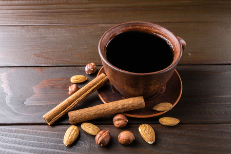 Hot black coffee in brown clay cup, almond, hazelnut and cinnamon stick on wooden background. Stock Photo