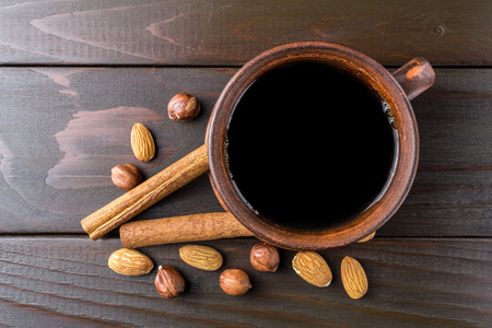 Hot black coffee in brown clay cup, almond, hazelnut and cinnamon stick on wooden background, top view. Stock Photo