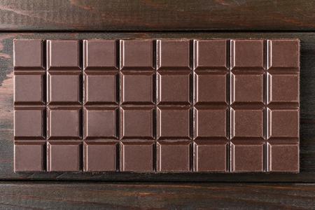 Bitter, dark chocolate bar on wooden planks background, top view.