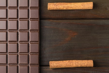 Bitter, dark chocolate bar and cinnamon stick on wooden background with space for text, top view. Stock Photo