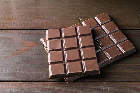 Bitter, dark chocolate bar on wooden planks background. Stock Photo