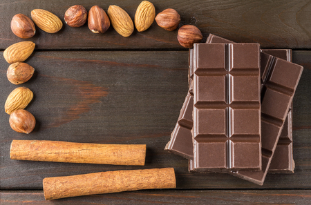 Bitter, dark chocolate bar, almond, hazelnut and cinnamon stick on wooden background with space for text, top view. Stock Photo