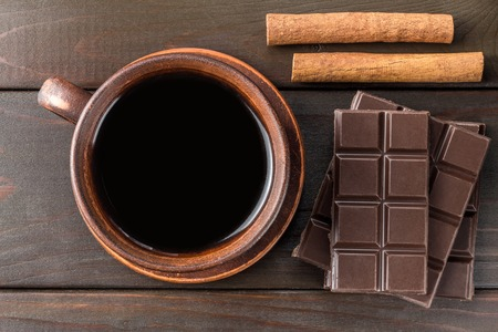 Hot black coffee in brown clay cup, dark chocolate bar and cinnamon stick on wooden background, top view.