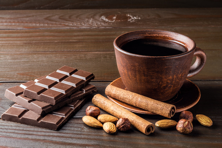 Hot black coffee in brown clay cup, dark chocolate bar, almond, hazelnut and cinnamon stick on wooden background. Stock Photo