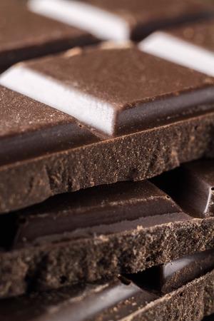 Bitter dark chocolate pieces on the heap, selective focus, macro image.