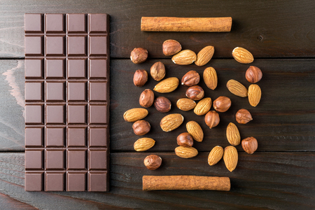 Bitter, dark chocolate bar, almond, hazelnut and cinnamon stick on wooden background, top view.