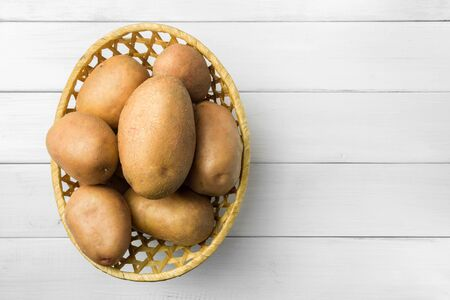 Uncooked, fresh crop of potatoes in a wicker basket on wooden table of white planks background, top view. Stock Photo
