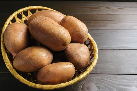 Uncooked, fresh crop of potatoes in a wicker basket on wooden table of dark brown planks background.