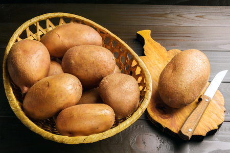 Uncooked, fresh crop of potatoes in wicker basket and cutting board with knife on wooden table of dark brown planks background.