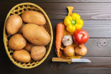 Fresh crop of potatoes in wicker basket and pepper, tomato, onion, garlic, carrot on cutting board, wooden table of dark brown planks, top view.