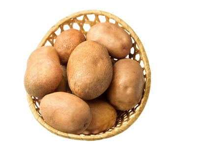 Uncooked, fresh crop of potatoes in a wicker basket isolated on white background.