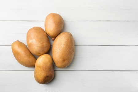 Uncooked, fresh crop of potatoes on wooden table of white planks background, top view.