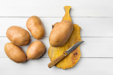 Uncooked, fresh crop of potatoes on cutting board with knife at wooden table of white planks background, top view.