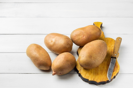 Uncooked, fresh crop of potatoes on cutting board with knife at wooden table of white planks background.
