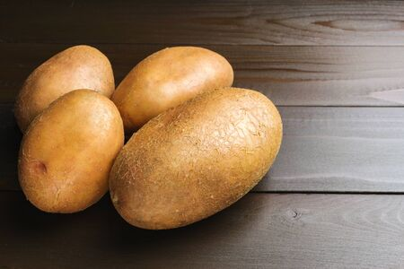 Uncooked, fresh crop of potatoes on wooden table of dark brown planks background, close-up view. Stock Photo