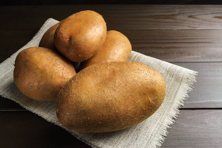 Uncooked, fresh crop of potatoes at cloth on wooden table of dark brown planks background, close-up view.
