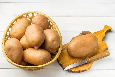 Uncooked, fresh crop of potatoes in wicker basket and cutting board with knife on wooden table of white planks background.