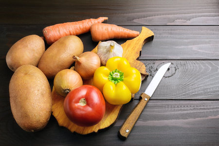 Fresh crop of vegetables, potato, pepper, tomato, onion, garlic, carrot at cutting board on wooden table of dark brown planks.
