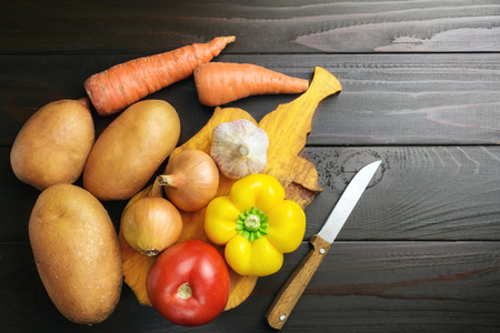 Fresh crop of vegetables, potato, pepper, tomato, onion, garlic, carrot at cutting board on wooden table of dark brown planks, top view.