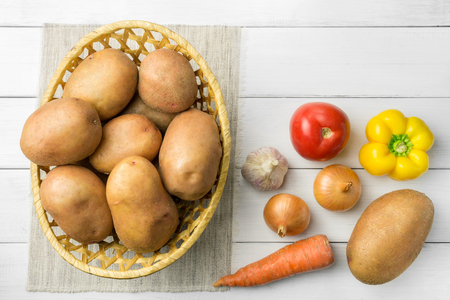 Fresh crop of potatoes in a wicker basket and pepper, tomato, onion, garlic, carrot on wooden table of white planks, top view.