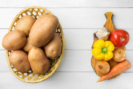 Fresh crop of potatoes in a wicker basket and pepper, tomato, onion, garlic, carrot on cutting board, wooden table of white planks, top view.