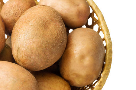 Uncooked, fresh crop of potatoes in a wicker basket isolated on white background, close-up view.