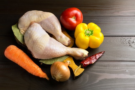 Two raw chicken legs on cutting board with spices and vegetables such as tomato, carrot, pepper, red chili pepper, onion at wooden dark brown planks. Stock Photo