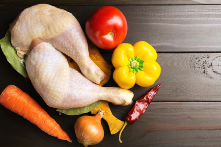 Two raw chicken legs on cutting board with spices and vegetables such as tomato, carrot, pepper, red chili pepper, onion at wooden dark brown planks, top view.