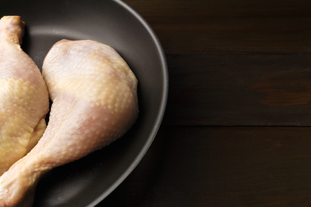 Two fresh and raw chicken legs in black frying pan at dark wooden planks, close-up view.