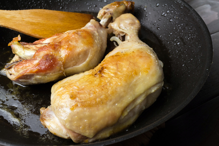 Two roasted chicken legs in black frying pan, close-up view. Stock Photo