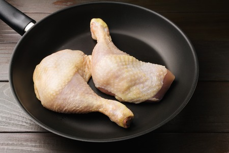 Two fresh and raw chicken legs in black frying pan on wooden dark brown planks.