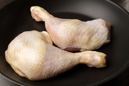Two fresh and raw chicken legs in black frying pan, close-up view. Stock Photo