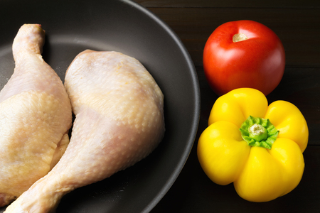 Two fresh and raw chicken legs in black frying pan, red tomato and yellow pepper on dark wooden planks, close-up view.