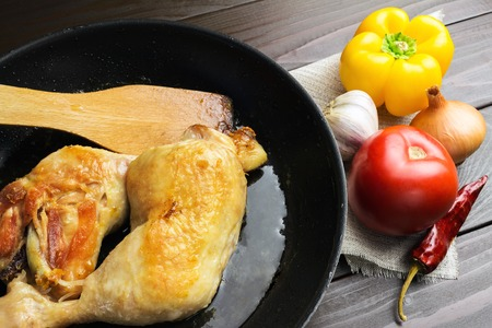 Two roasted chicken legs in black frying pan with vegetables and spices on dark wooden planks close-up view.