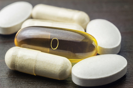 White capsules of glucosamine, yellow capsules of omega-3, white pills of calcium on wooden table, macro image.