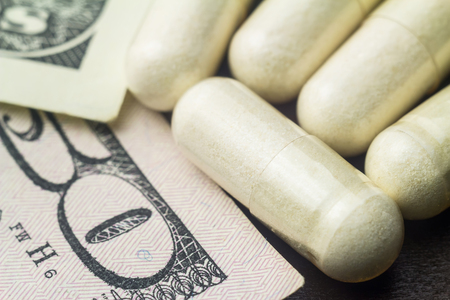 White capsules of glucosamine chondroitin, healthy supplement pills on dollar banknote, macro image. Stock Photo